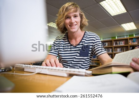 Student studying in the library with computer at the university - stock photo
