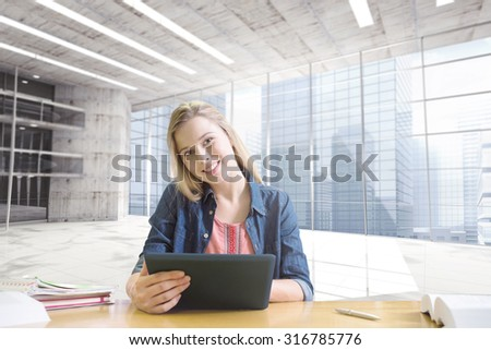 Student studying in the library with tablet against modern room overlooking city - stock photo