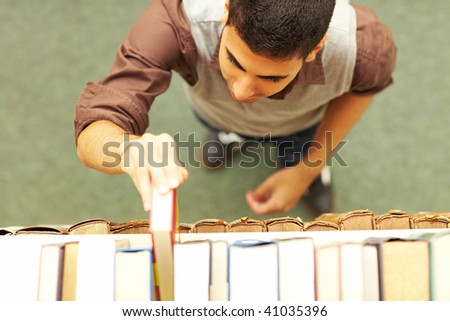 Student taking a book from shelf in library - stock photo