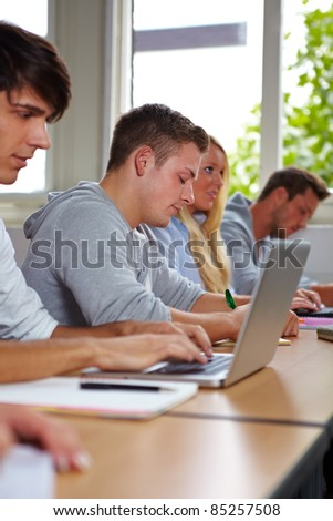 Student taking notes at laptop in university class - stock photo