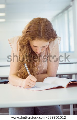 Student taking notes in class at the college - stock photo