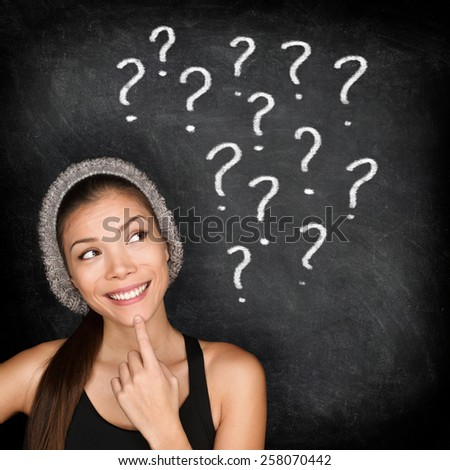 Student thinking with question marks on blackboard. Asian female young adult university or college student looking up at written drawings of question marks on chalkboard wondering career choices. - stock photo