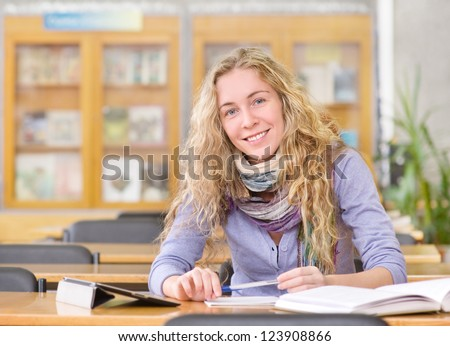 student using a tablet computer in a library - stock photo