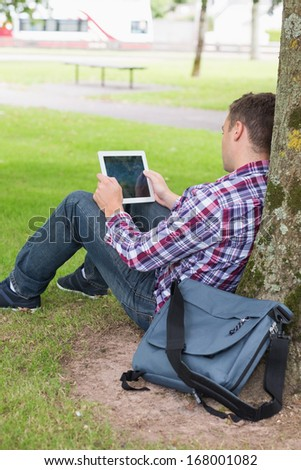Student using his tablet pc outside leaning on tree on college campus - stock photo