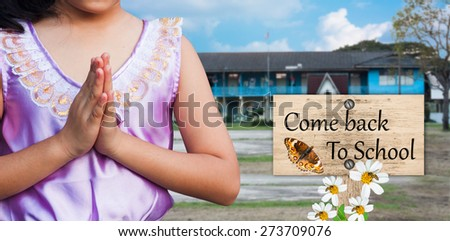student wear uniform Thai gesturing in front of the school building  with signpost in beautiful come back to school - stock photo