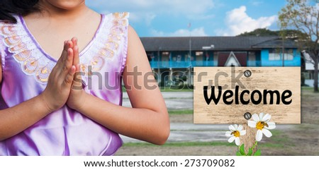 student wear uniform Thai gesturing in front of the school building  with signpost in beautiful  welcome back to school - stock photo