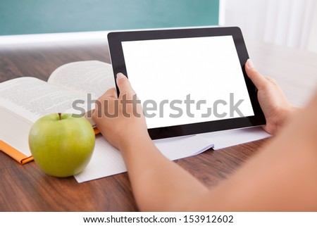 Student with apple and book on desk holding digital tablet - stock photo