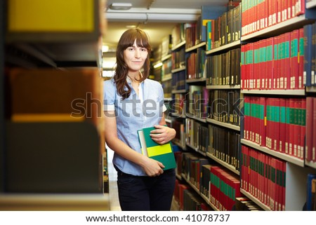 Student with book leaning on shelf in library