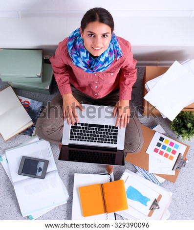 Student with books spread around working on a laptop - stock photo