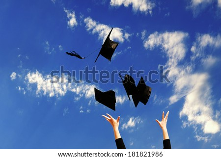 Student with congratulations throwing graduation hats in the air celebrating - stock photo