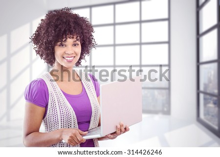 Student with laptop against room with large window showing city - stock photo