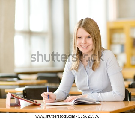 student with tablet computer in library. looking at camera - stock photo