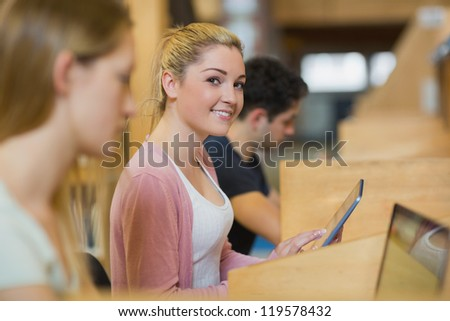 Student with tablet pc looking up from studying and smiling in college library - stock photo