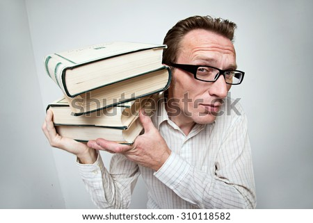 student with the hard pile of books on his shoulder. concept the hard study - stock photo