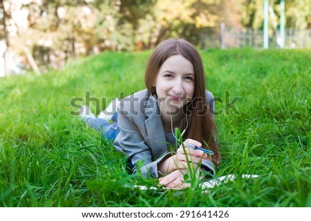 Student with white headphones lying on the green grass