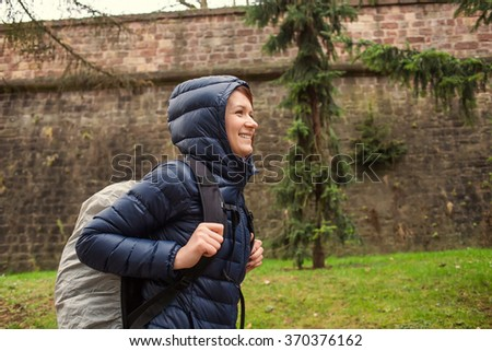 Student woman hiking in forest. Female hiker smiling happy portrait on rainy day during a trekking trip. Pretty young girl outdoors in nature. - stock photo