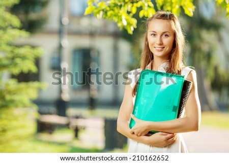 Student woman is standing with the folder and copy-book on the university campus background at the start of a school year in college. Happy smart young woman is going to study outdoors in the park.