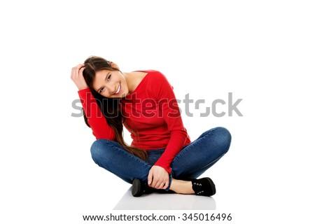 Student woman sitting cross legged on the floor. - stock photo