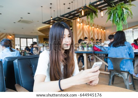 Student women texting chat on smartphone in coffee at library of university
