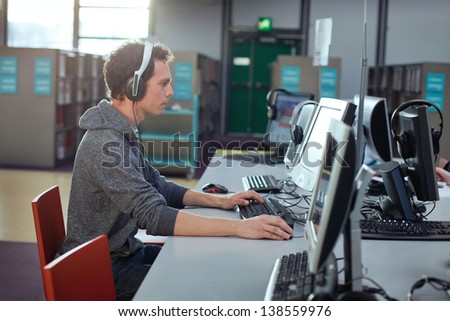 student working at the computer in the library - stock photo