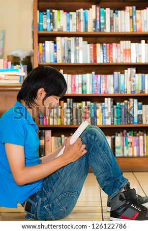 Student - Young man sits in library on the floor learning reading a book - stock photo