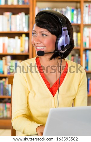 Student - Young woman in library with laptop and headphones learning and smiling - stock photo