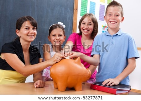Students and teacher saving money by putting big coin into piggy bank