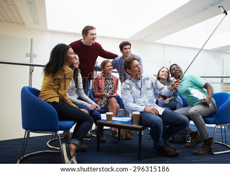 Students And Tutors Taking Portrait With Selfie Stick - stock photo