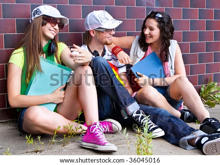 students are sitting beside a wall and making a rest - stock photo