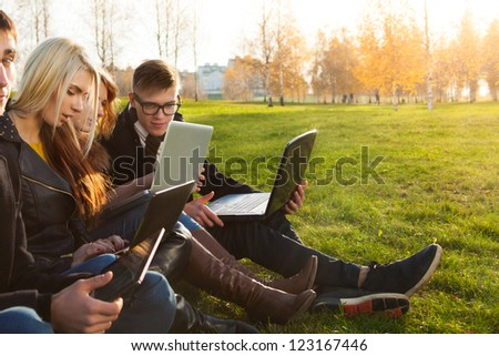 students browsing internet in sunny park - stock photo