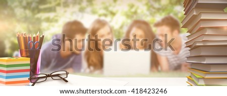 Students desk against happy students using laptop outside - stock photo