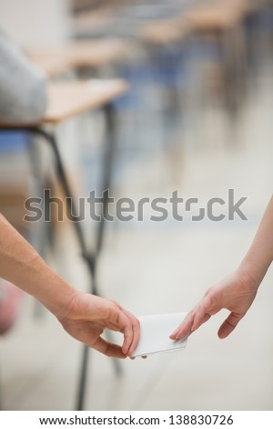 Students doing a test while sitting at a table in a classroom and cheating - stock photo