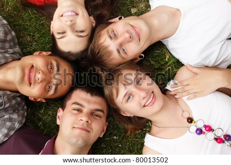 students faces happy friends group lying on green grass