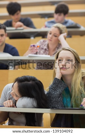 Students feeling bored in a lecture hall in college - stock photo