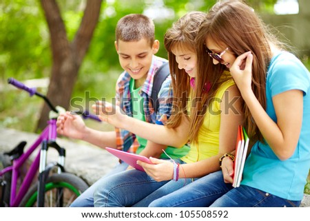 Students hanging out together watching funny staff on the screen of the tablet computer - stock photo
