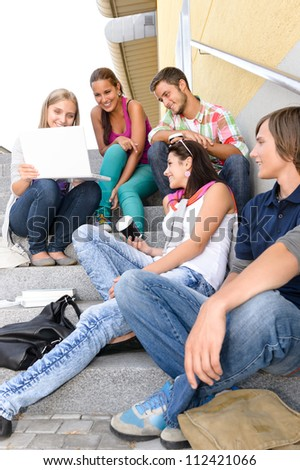 Students having fun with laptop school stairs teens college laughing - stock photo