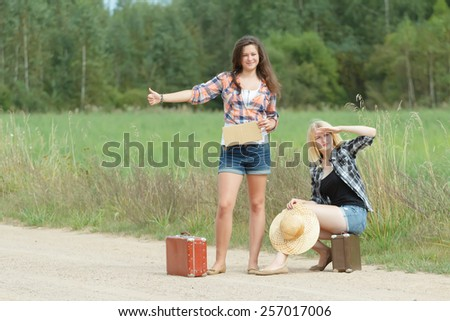 Students hitchhikers with cardboard on a country road - stock photo
