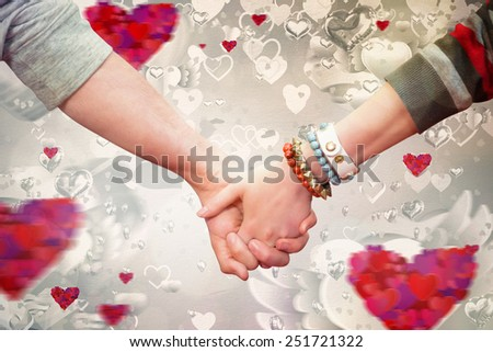 Students holding hands against love heart pattern - stock photo