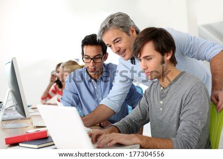 Students in class with teacher helping with work - stock photo