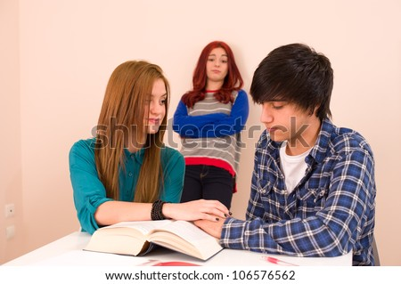 Students in classroom, jealous girl looking at a couple - stock photo