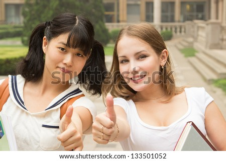 Students in park smiling and showing happy thumbs up success sign. Asian Caucasian women university student holding books outside - stock photo