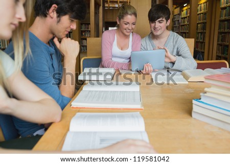 Students in the library studying with two using tablet pc in college