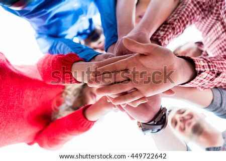 Students learning and stacking hands together, low angle perspective
