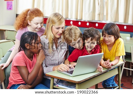 Students learning with laptop computer in elementary school class - stock photo