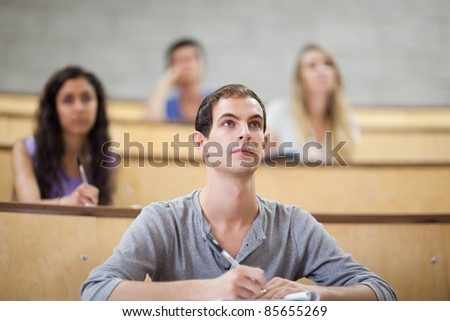 Students listening during a lecture in an amphitheater - stock photo