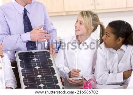 Students listening to teacher explaining solar panel and wind turbines in classroom - stock photo