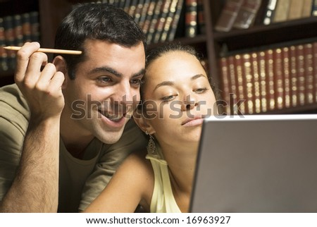 Students looking at laptop computer, he is smiling, she looks serious. Horizontally framed photo. - stock photo
