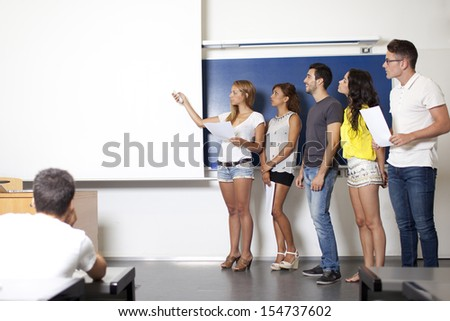 students making a presentation at blackboard