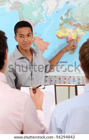Students observing a world map - stock photo