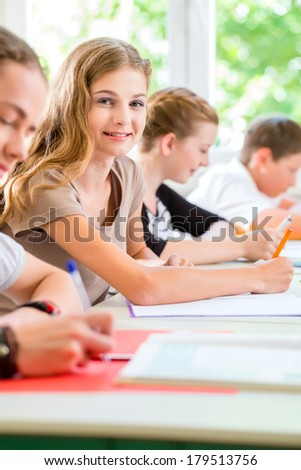Students or pupils of school class writing an exam test in classroom concentrating on their work
